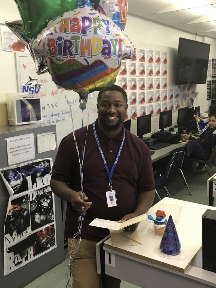 HOW OLD ARE YOU NOW? Digital Design teacher Anthony Bell gets ready to blow out his candles as students shower him with birthday gifts.
