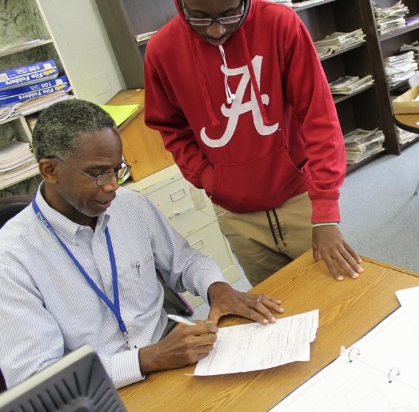WEEKLY CHECKUP: Multimedia Academy student and Hurricanes football player Donovan Gilbert has his Progress Report completed while getting feedback from Journalism instructor C.B. Hanif.
