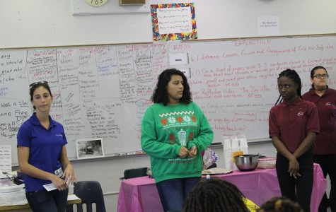 SGA HOLIDAY SPIRIT: Student Government Association officers, Karla Lopez and  Joudeline Altidor presented Urban Youth Impact staff member, Michelle Cyr,  with a generous Christmas donation to help give gifts to the children who don't have a happy Christmas because they can't get presents.
