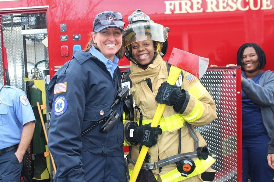 LOOKING LIKE A PRO: Firefighter/Paramedic Leigh Cottrell, left, helps Taylor Douglas get a feel for the profession during firefighters visit to Inlet Grove Jan. 21. It was actually fun, Taylor said. The suit was heavy, I got a feel of what the firefighters go through. Im glad I tried it.