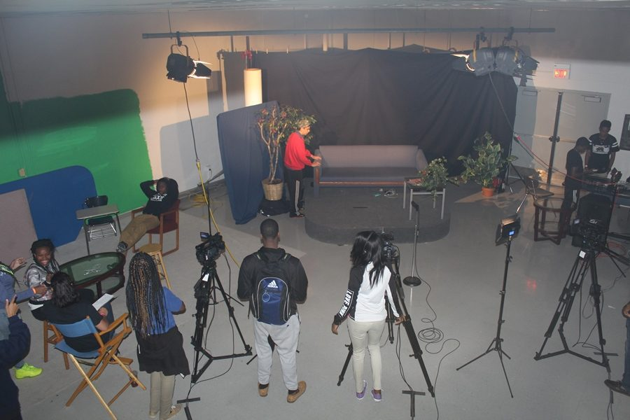 SETTING THE STAGE: Students set up the lights, camera, and stage to reenact a scene from the 90s sitcom Martin.