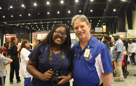 TAKING THE MESSAGE TO THE MASSES: Medical Academy freshman and journalist Brianna Luberisse joined Principal Jack Myszkowski as Inlet Grove staff provided information to students and their families during the annual Showcase of Schools Oct. 18.