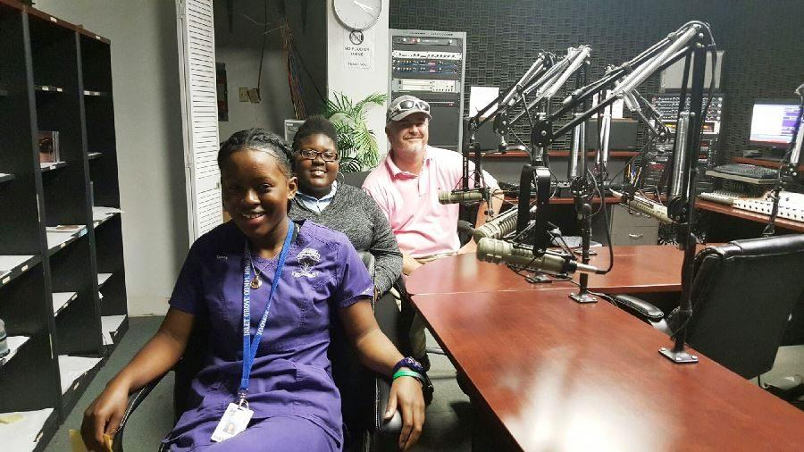 BROADCASTING LIVE: Joining Brother Carl in the FM 107.1 radio studio Feb. 7 to share information about the great things going on with the Inlet Grove family were Business/Career Coordinator Scott McDermott; the Medical Academys Nurse Blair (not pictured); Junior Class and School Improvement Club President Tanoy Thames (left); and GroveWatch Editor-in-Chief Brianna Luberisse.