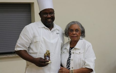 """1ST PLACE CUISINE: The Rev. Michael Wilson, father of the Hurricanes' own Digital Design Instructor Anthony Bell, accepts the winning trophy for his winter squash dish from President Arneatha Roberts as The greater Palm Beaches Business and Professional Women's Club, Inc. featured a dozen of """"The Best Cooks in Palm Beach County"""" at their 20th Annual Men's Cookery event. The coconut cake, ham and macaroni and cheese were particular hits as other chefs won awards for their tasty dishes Feb. 25 at the Salvation Army in West Palm Beach."""