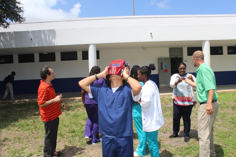 Students take turns viewing the eclipse through the helmet.