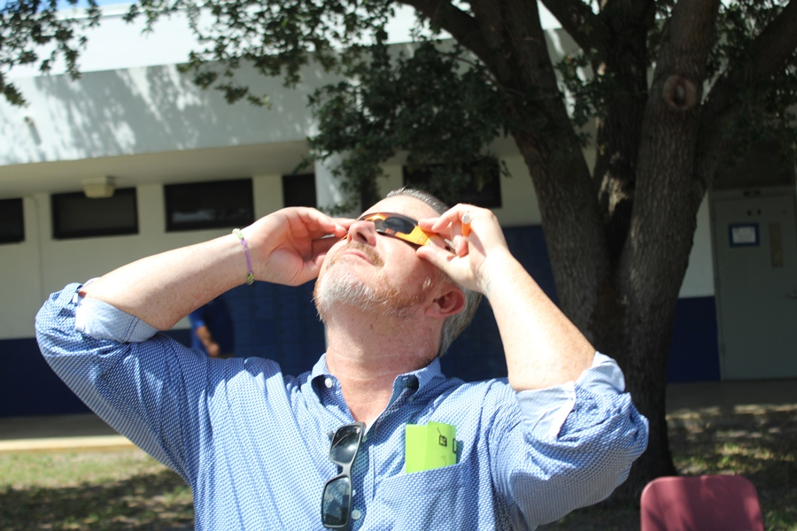 Mr. McDermott trades his shades for eclipse glasses.