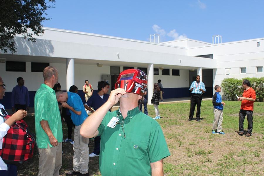 Mr. Miller tries the welding helmet.