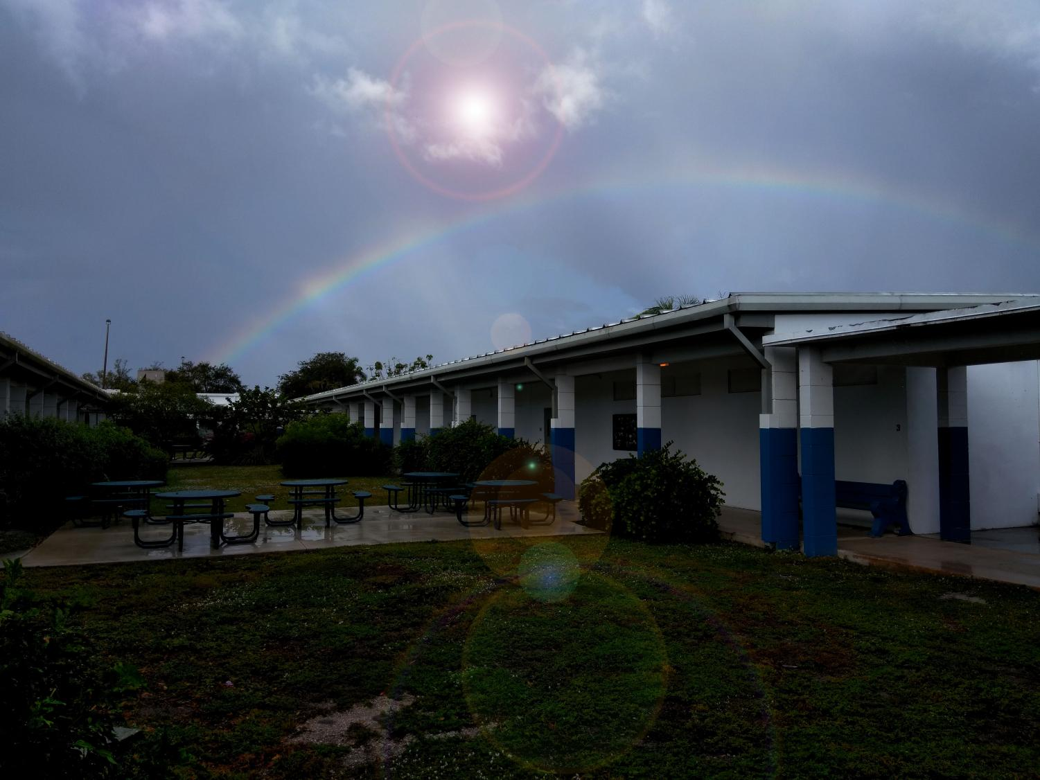 COMES THE RAINBOW: Humid and hot after a series of morning showers, Inlet Grove's campus is cradled beneath a shining sun and a radiant rainbow arch.