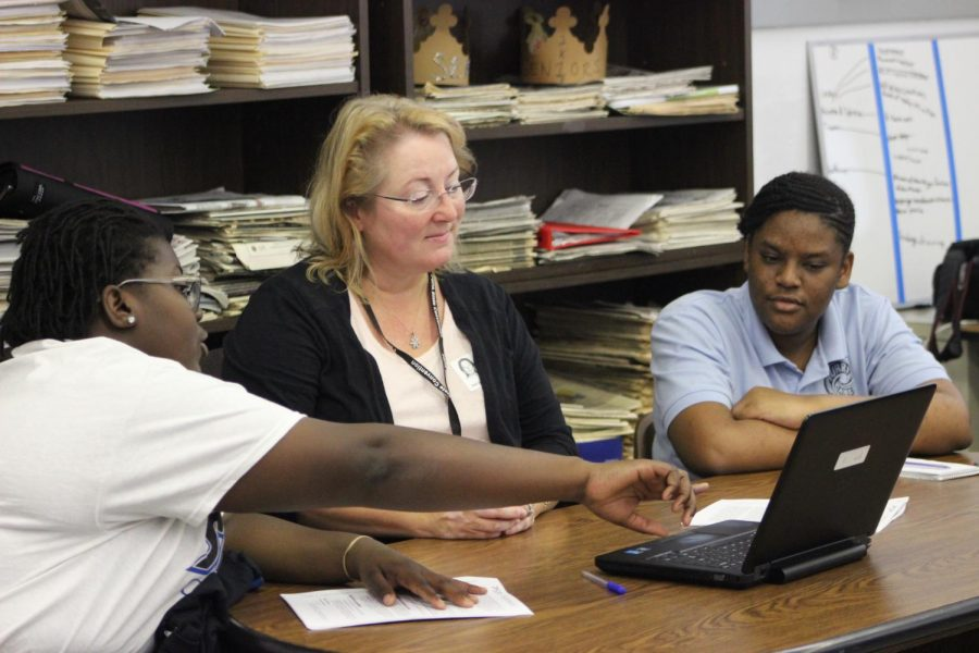 GRADUATION BOOK:  Editor-in-Chief Brianna Luberisse (left) and Co-Editor Brianna Dwyer confer with Walsworth yearbook company representative Tamara Moore (center) on ideas and designs during the Journalism class as the publications staff continue working to document the Canes 2019-2020 year.