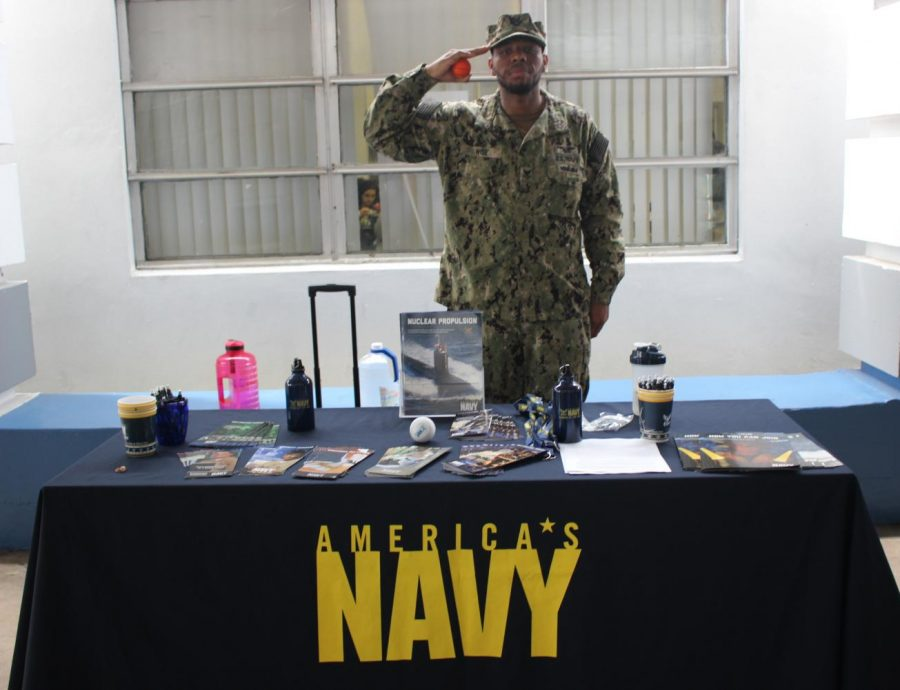 BRIDGING THE GAP: Operation Specialist William Wise enlightens student Jalen Giles on the possibilities and oppurtunities available afforded by the U.S Navy through brochures and  pamphlets while showcasing U.S Navy souvenirs.