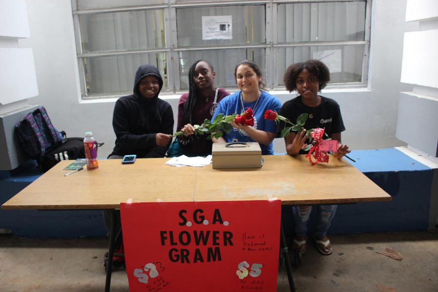 BE+MINE%3A+SGA+director+Mrs.+Pietenza+accompanies+students+Jalen+Giles%2C+Yardine+Chocetene%2C+and+Alyssa+Stephens+while+selling+Valentine%27s+Day+flower+grams+to+students.