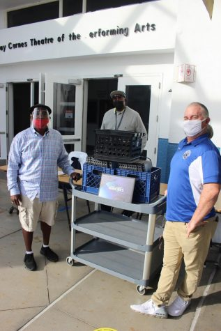 GIVING HELP TO THE KIDS: Mr. Banks (from left), Mr. Al and Mr. McDermott handed out the laptops to get students ready for their career classes next semester.