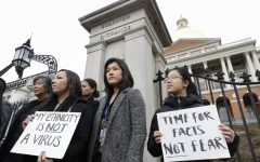 Jessica Wong, of Fall River, Mass., front left, Jenny Chiang, of Medford, Mass., center, and Sheila Vo, of Boston, from the state's Asian American Commission, stand together during a protest, Thursday, March 12, 2020, on the steps of the Statehouse in Boston. Asian American leaders in Massachusetts condemned what they say is racism, fear-mongering and misinformation aimed at Asian communities amid the widening coronavirus pandemic that originated in China.