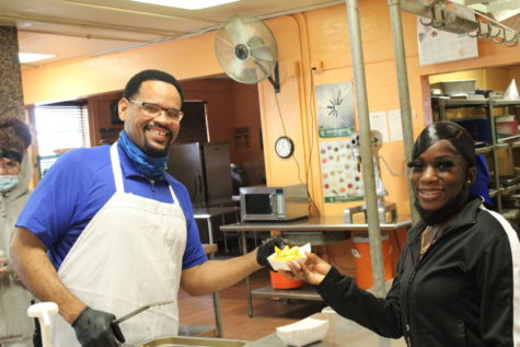 HOORAY: Today the students with at least 200 Hero Points got to receive a special incentive during lunch that was provided by the staff. Lowicha, a senior in the Medical Academy gets the fries for the COO, Mr. Sims.
